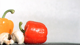 Peppers and mushroom watered in super slow motion Footage