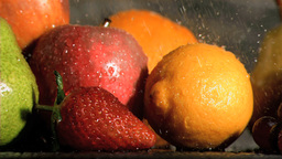 Rain falling in super slow motion on many fruits Footage