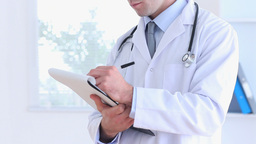 Smiling doctor writing on a clipboard Stock Video Footage