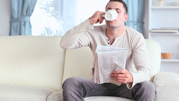 Man drinking a coffee while reading the news Stock Video Footage