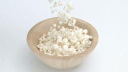 Popcorn in super slow motion falling in a wooden b Footage