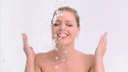 Happy woman in slow motion splashing her face Footage
