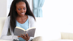 Woman reading a book while smiling Footage