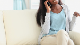 Woman sitting on a couch while talking on the phon Footage