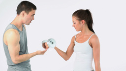 Trainer helping a woman to lift weights Footage