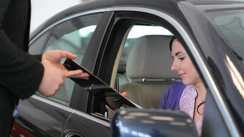 Woman in her car signing a document Stock Video Footage