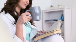 Woman drinking a coffee while she is reading Footage