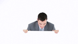 Businessman hiding beside a board Stock Video Footage