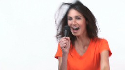 Happy woman dancing and singing into a micro Stock Video Footage