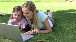 Mother and his daughter using a laptop in a park Stock Video Footage