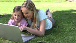 Mother and his daughter using a laptop in a park Footage