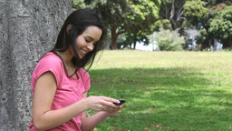 Smiling woman using a mobile phone in a park Stock Video Footage