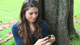 Woman texting in a park Stock Video Footage