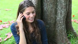 Woman calling leaning against a tree Footage
