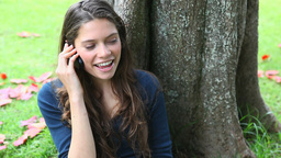 Smiling woman calling in a park Footage