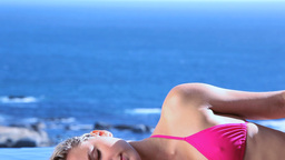 Woman lying on side while tanning Footage