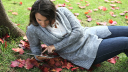 Woman using an ebook in a park Footage