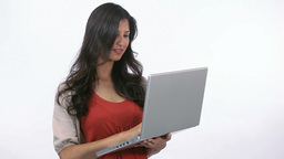 Woman using a laptop while holding it Stock Video Footage