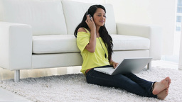 Woman listening music while using a laptop Footage