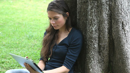 Woman using a tablet computer in a park Stock Video Footage