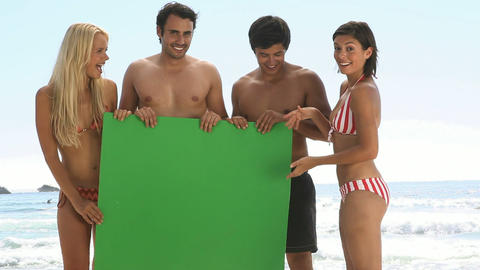 Friends holding a green board on the beach Footage