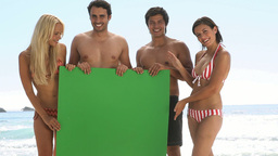 Friends holding a green board on the beach Stock Video Footage