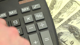 Hand typing on a calculator surrounded by bills Stock Video Footage