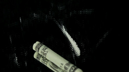 Line of cocaine and a folded dollar bill spinning Live Action