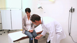 Doctor testing knees reflex of a patient Stock Video Footage