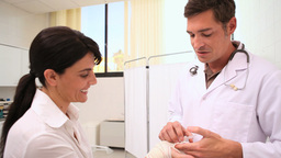 Doctor doing a bandage at the hand of a patient Footage
