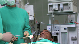 Surgeon doing an operation while holding surgical  Footage