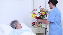 Serene senior woman speaking at a nurse who gives  Footage