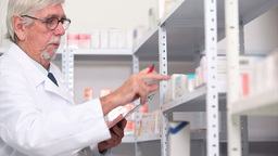 Pharmacist looking at pills in a shelf Footage