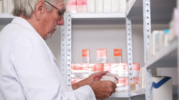 Pharmacist looking at pills in a shelf with a clip Stock Video Footage