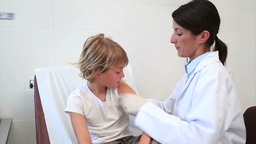 Child sitting on a bed receiving an injection Stock Video Footage