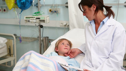 Child lying on a bed next to a doctor Stock Video Footage