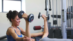 Female trainer helping woman lift weights Footage