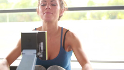 Woman working out on row machine Stock Video Footage