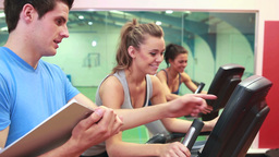 Trainer teaching two women on exercise bikes Footage