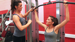 Trainer helping woman on weights machine Stock Video Footage