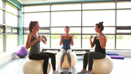 Women sitting on exercise balls lifting weights Footage