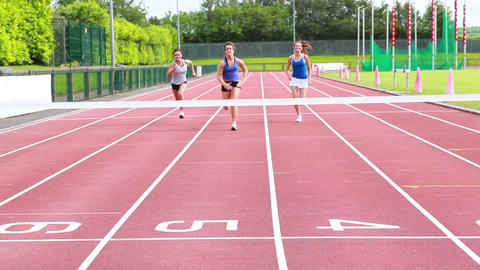 Three woman running on a track and crossing finish Footage