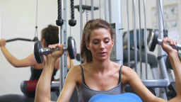 Trainer helping lying woman lifting weights Stock Video Footage