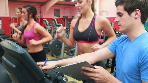 Trainer talking to woman on treadmill Stock Video Footage