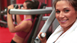 Woman using weights machine and smiling Footage