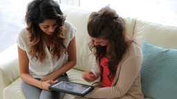Woman showing friend tablet tc Footage