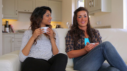 Friends sitting on the couch drinking coffee Footage