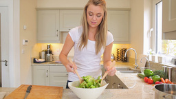 Woman mixing salad in the kitchen Stock Video Footage