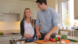 Man preparing vegetables for pregnant wife Footage