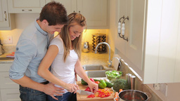Woman cutting salad with man holding her from behi Stock Video Footage